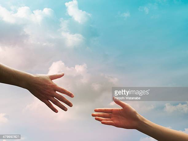 two hands seem to reach together in the sky - reaching stock pictures, royalty-free photos & images