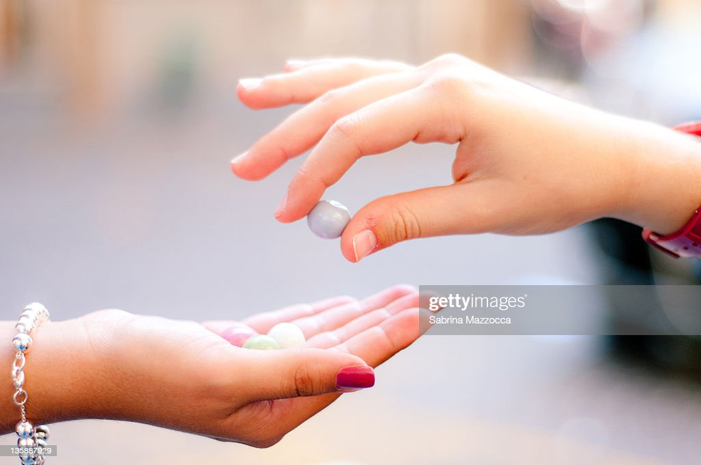 Two hands sharing candies : Stock Photo