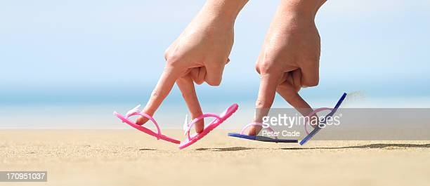 two hands with flip flops on fingers on beach - focus on foreground stock pictures, royalty-free photos & images