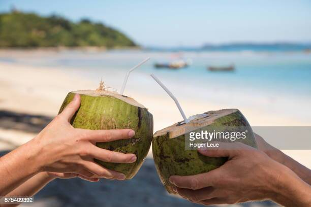 Two hands with fresh drinking coconuts at Maung Shwe Lay village, near Ngapali, Thandwe, Myanmar