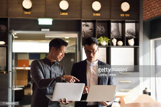 two handsome chinese men standing with laptops in an office - asia stock pictures, royalty-free photos & images