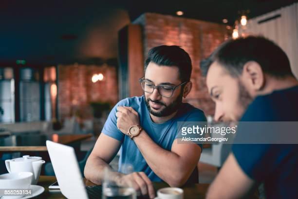 dois amigos bonitos beber café e navegar na net no restaurante cafe - duas pessoas - fotografias e filmes do acervo