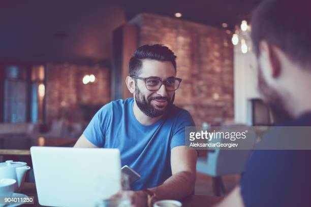 Two Handsome Friends Drinking Coffee and Surfing the Net In Coffee Restaurant
