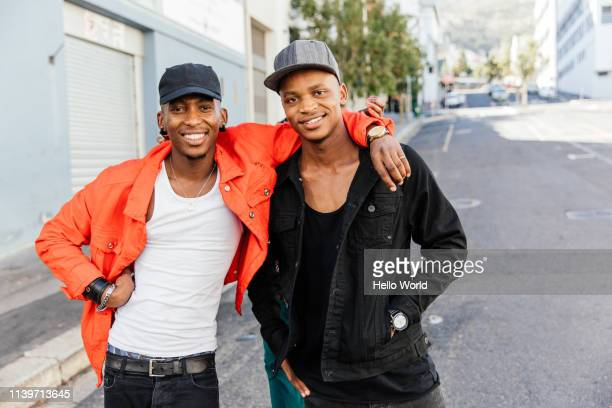 Two handsome happy embracing friends smiling into camera on city street