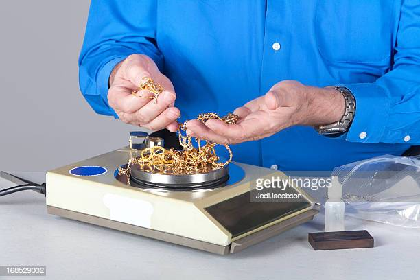 two handy holding and weighing scrap gold - oversized necklace stock pictures, royalty-free photos & images