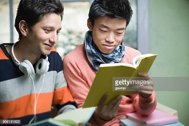 Two happy Asian, teenage, student friends reading book near window.