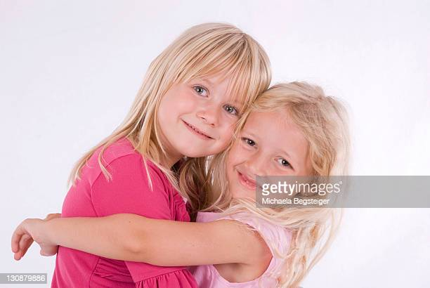 Two happy, blonde girls hugging