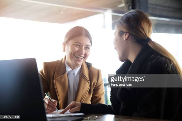 two happy business woman talking - cashier stock pictures, royalty-free photos & images