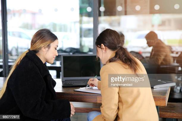 Two happy business woman talking