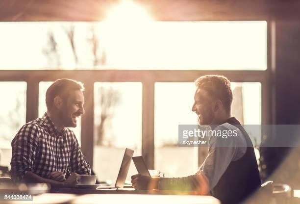Zwei glückliche Geschäftsleute kommunizieren während der Arbeit in einem Café.