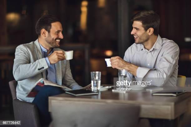 dois empresários felizes bebendo café e comunicando-se no café. - pausa para o café - fotografias e filmes do acervo