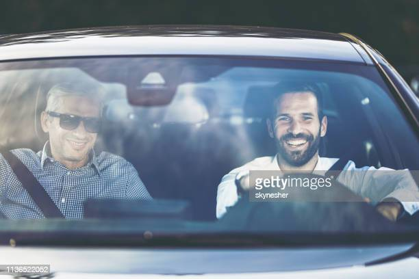 two happy businessmen going on business travel by car. - windshield stock pictures, royalty-free photos & images