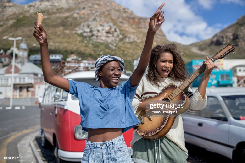 Two happy carefree female friends with guitar and ice cream cone at a van : Stock Photo