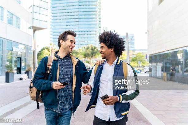 two happy casual businessmen with cell phones meeting in the city, barcelona, spain - gemeinsam gehen stock-fotos und bilder