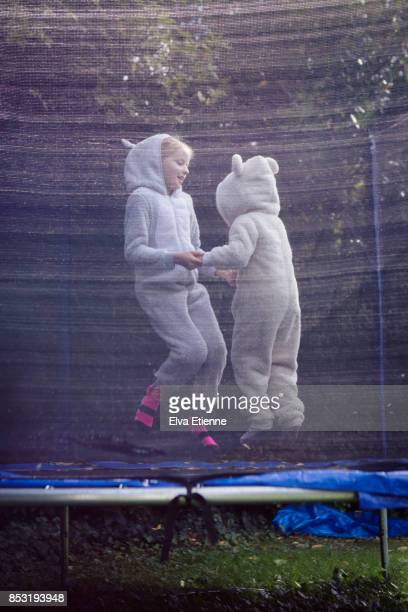 Two happy children in bear suit onesies bouncing on a trampoline