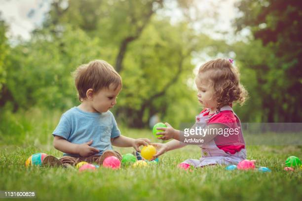 two happy children playing in summer park - sharing stock pictures, royalty-free photos & images