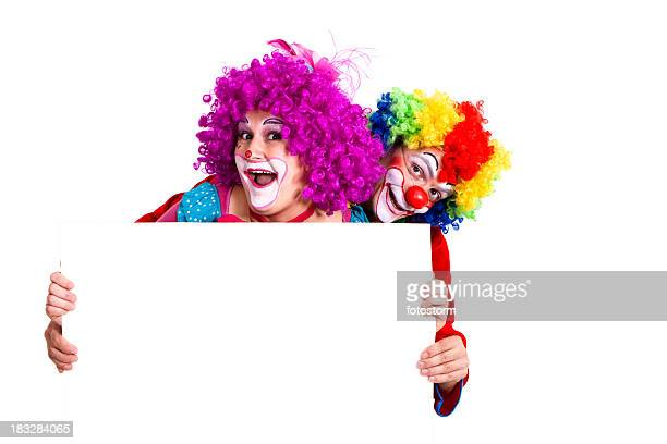 Two happy clowns holding blank banner with copy space