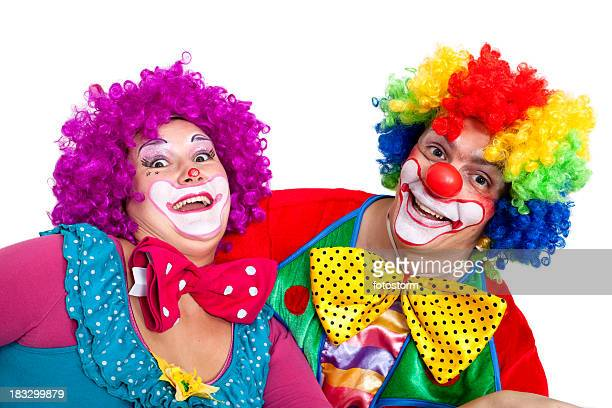 two happy clowns making faces on white background - happy clown faces stock photos and pictures