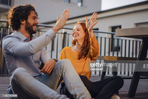 two happy colleagues high fiving on roof terrace - colleague stock-fotos und bilder