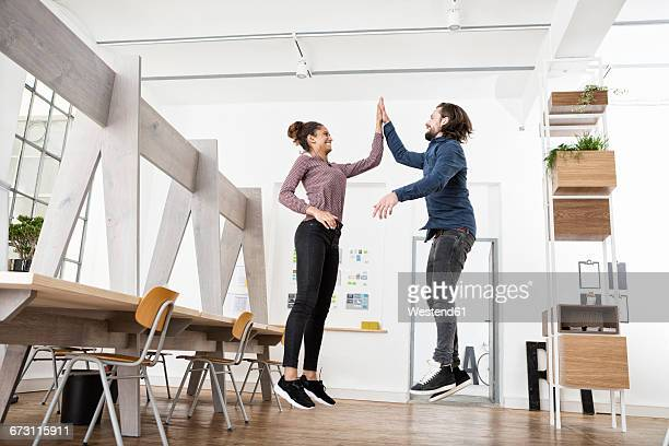 Two happy colleagues in office jumping and high fiving