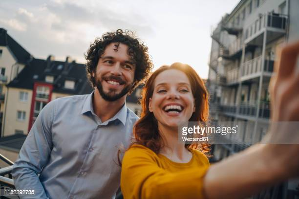 two happy colleagues on roof terrace taking a selfie - 30 39 jaar stockfoto's en -beelden
