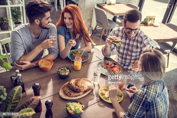 Two happy couples having a healthy meal in a restaurant and talking among themselves.