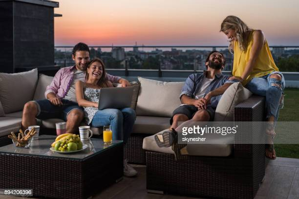 Two happy couples relaxing on sofa at penthouse balcony.