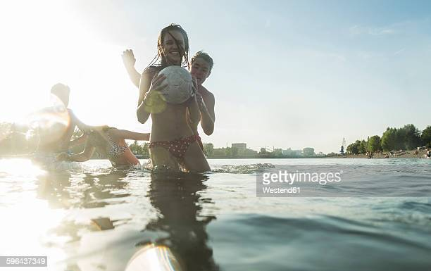 Two happy couples with ball in water