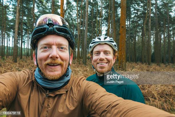 two happy cyclists taking selfie in forest - friendship stock pictures, royalty-free photos & images