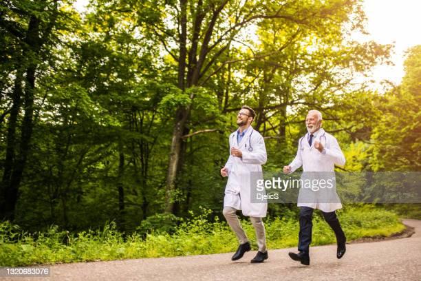 due dottori felici che corrono nella natura. - fuggire foto e immagini stock