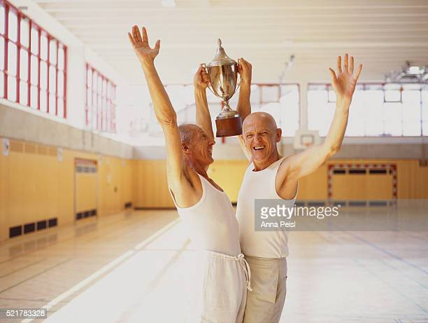 Two Happy Elderly Men with Trophy in Gym