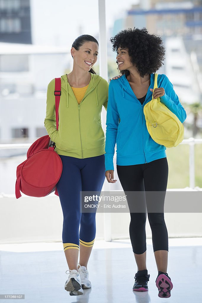 Two happy female friends carrying gym bags : Stock Photo
