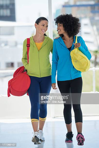 two happy female friends carrying gym bags - gym bag stock pictures, royalty-free photos & images