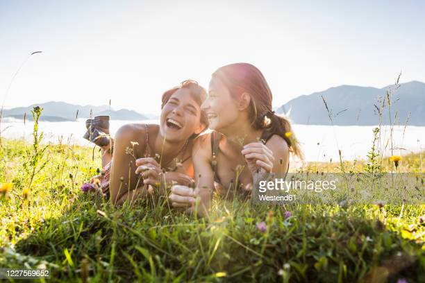 two happy female friends lying on a meadow in the mountains, achenkirch, austria - austria stock pictures, royalty-free photos & images