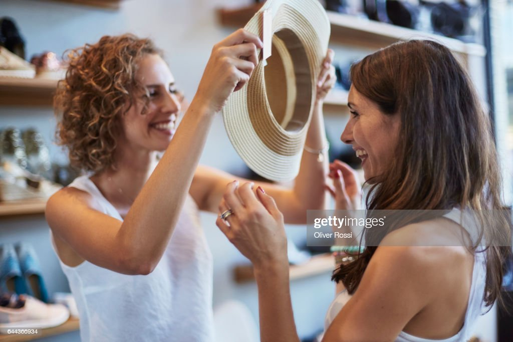 Two happy female friends shopping for a hat in a boutique : Stockfoto