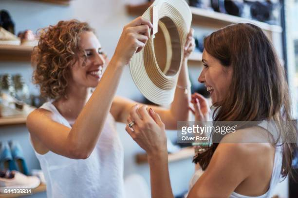 two happy female friends shopping for a hat in a boutique - only mid adult women stock pictures, royalty-free photos & images