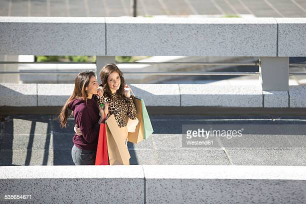 Two happy female friends with shopping bags