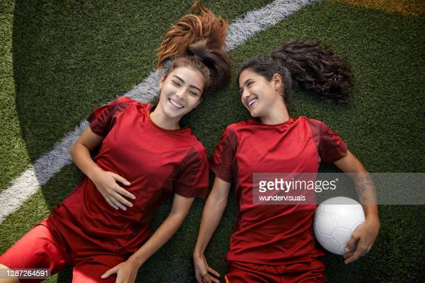two happy female soccer teammates relaxing lying on the grass - sporting term stock pictures, royalty-free photos & images