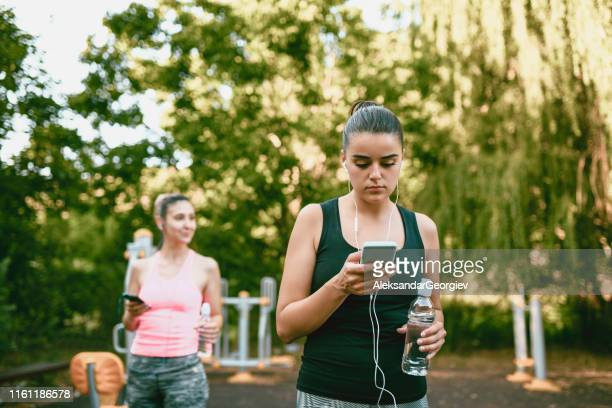 two happy females setting up playlists for workout - colors soundtrack stock pictures, royalty-free photos & images