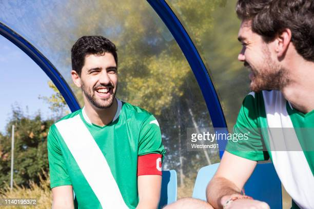 two happy football players sitting on bench at football field talking - チームキャプテン ストックフォトと画像