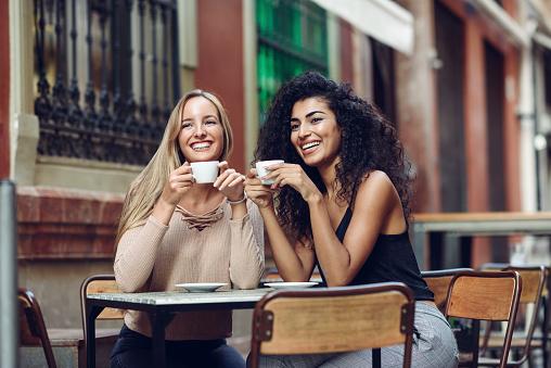Two happy friends drinking coffee in sidewalk cafe - gettyimageskorea
