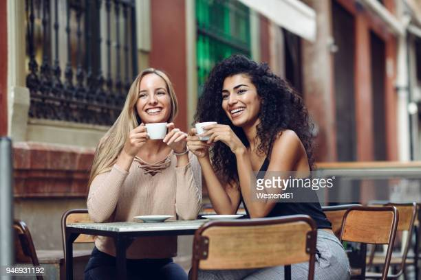 two happy friends drinking coffee in sidewalk cafe - pavement cafe stock pictures, royalty-free photos & images