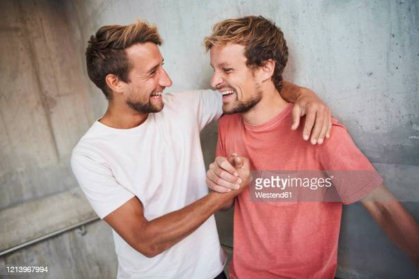two happy friends embracing and shaking hands - mid adult men stock-fotos und bilder