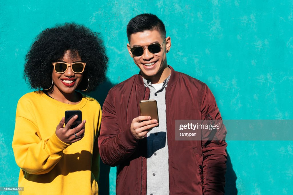 Two happy friends using the mobile in the street. : Stock Photo