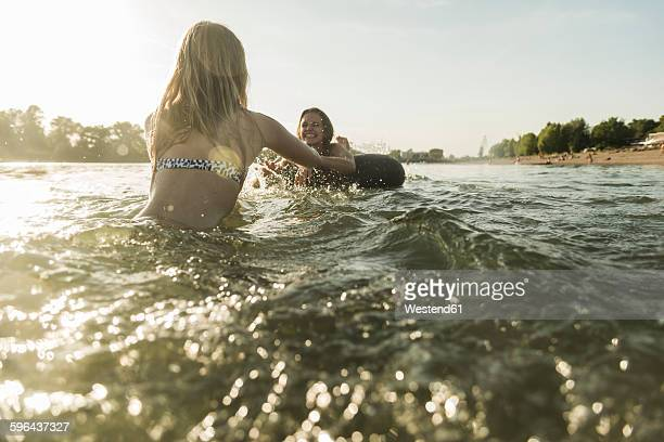 Two happy friends with inner tube in water