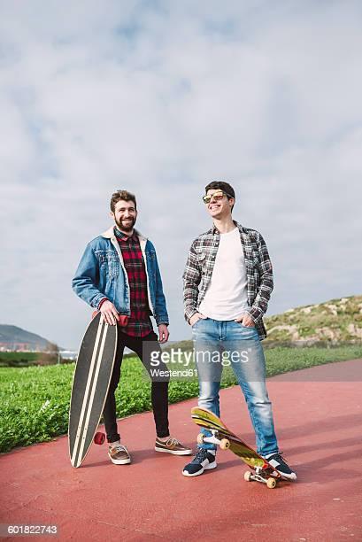 Two happy friends with longboard and skateboard