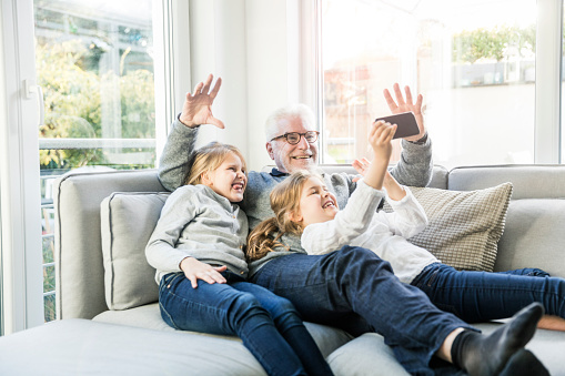 Two happy girls and grandfather on sofa taking a selfie - gettyimageskorea