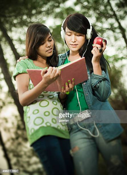 Two happy girls from different ethnicity studying together in nature.