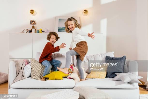 two happy girls jumping on couch at home - spielerisch stock-fotos und bilder