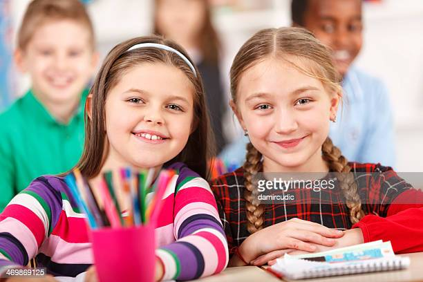 Two Happy Girls Smiling Together In The Classroom